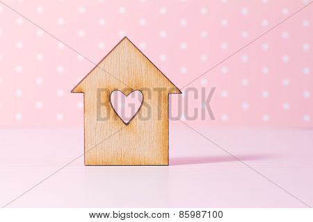 Wooden House With Hole In The Form Of Heart On Pink Background