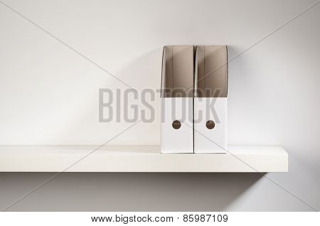 An empty document organizer placed on a shelf.
