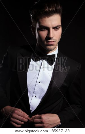 image of a handsome young business man looking away from the camera while closing his jacket.
