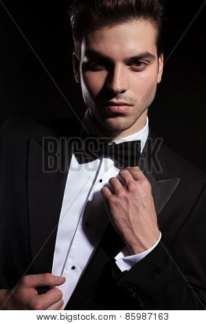 Close up portrait of a handsome young business man fixing his bowtie while looking at the camera.