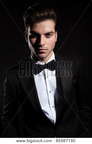 Portrait of a elegant young business man looking at the camera, on black background.