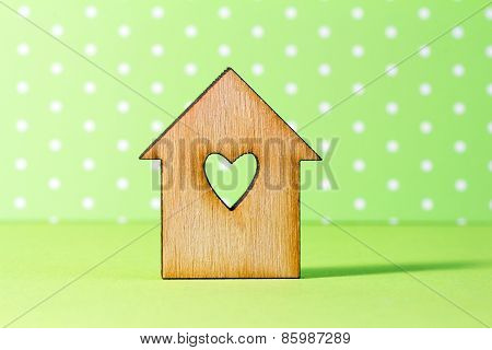 Wooden House With Hole In The Form Of Heart On Green Background