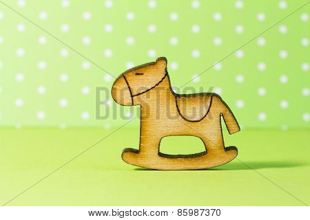 Wooden Icon Of Children's Rocking Horse On Green Background