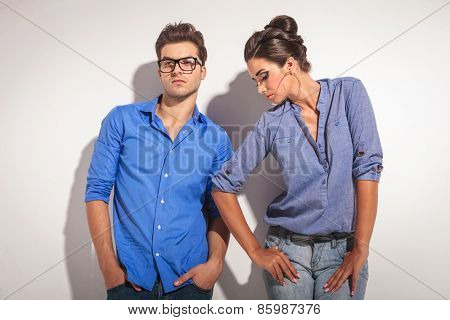 Young fashion couple leaning on a grey wall while looking away from the camera.