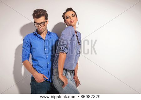 Handsome fashion man looking down while his lover is posing with her thumbs in pockets.