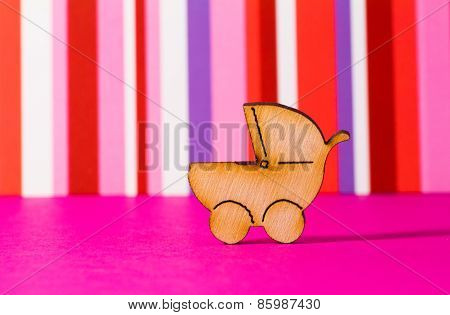 Wooden Icon Of Baby Carriage On Red Striped Background