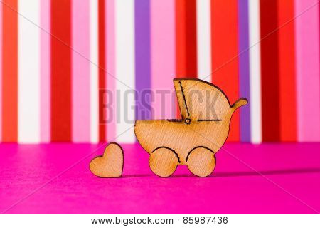 Wooden Icon Of Baby Carriage And Little Heart On Red Striped Background