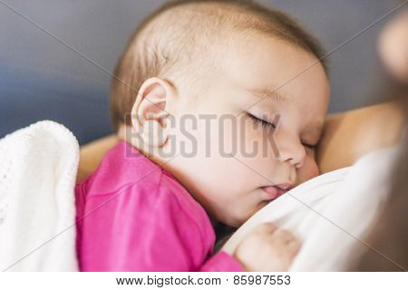 Little Cute Caucasian Infant Sleeping On Mothers Hands Indoors.