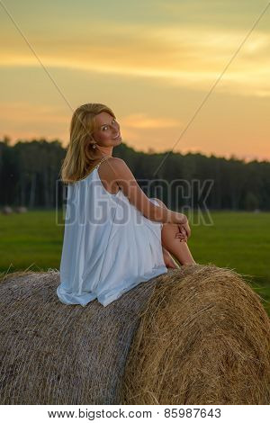 Blond woman posing at sunset time on a field