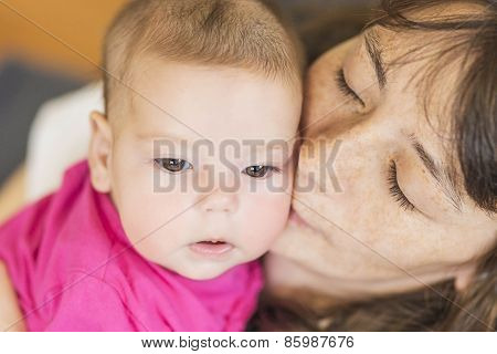 Cute Portrait Of Mother Kissing Her Little Newborn Girl.