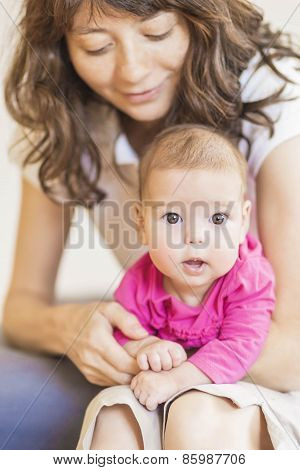 Family Concept: Portrait Of Young Mother Taking Care Of Her Little Newborn Infant Baby Indoors.