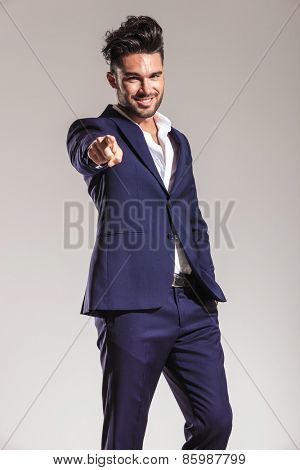 Confident young business man holding one hand in his pocket while pointing at you.