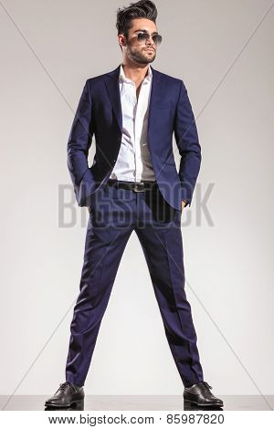 Full body picture of a handsome young business man holding both hands in his pocket, looking away from the camera.