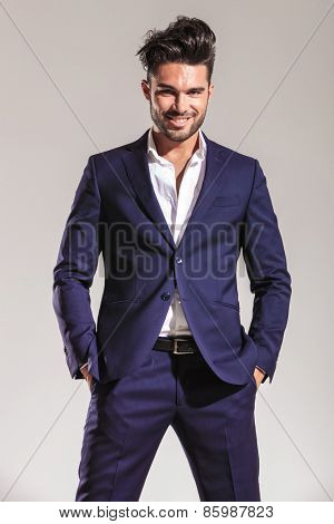 Handsome young business man smiling at the camera while holding both hands in his pocket.