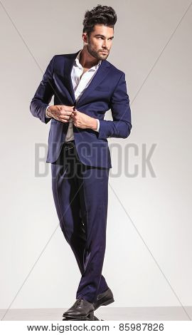 Full length picture of a handsome young business man closing his coat while looking away from the camera.