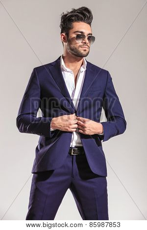 Attractive young business man looking away from the camera while closing his jacket.