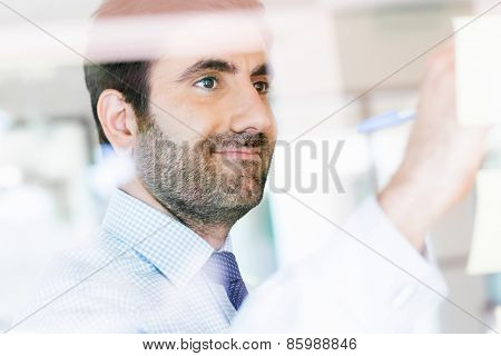 Young businessman in office looking at the notes