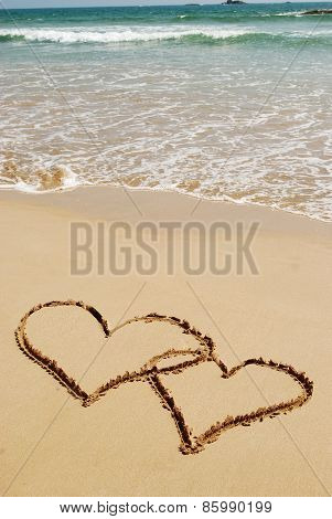 couple drawing a heart on wet golden beach sand