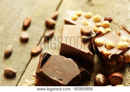 Still life with set of chocolate with nuts on wooden table, closeup