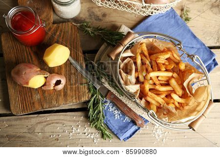 Tasty french fries in metal basket on wooden table background