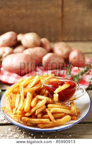 Tasty french fries on plate, on wooden table background