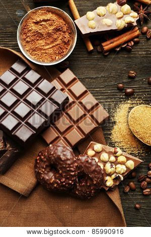 Still life with set of chocolate, nuts and spices on wooden table, top view