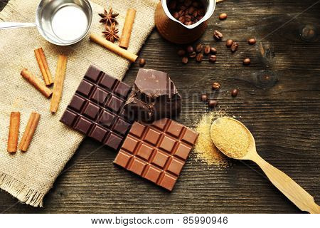 Still life with set of chocolate with spices on wooden background