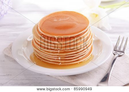 Delicious pancakes with honey on plate on table close-up
