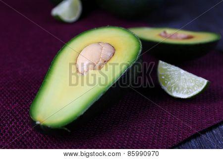 Sliced avocado on purple mat, closeup