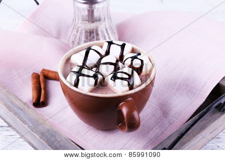 Cup of cocoa with marshmallows on tray with napkin, closeup