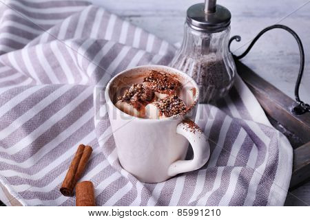 Cup of cocoa with marshmallows on tray and stripped napkin, closeup