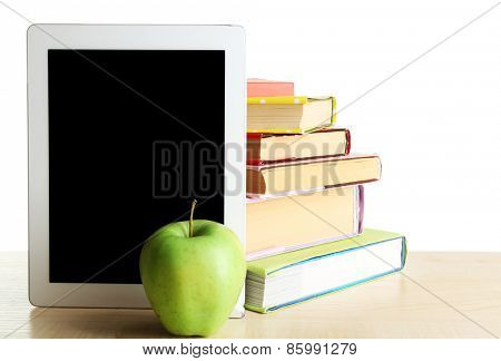 Books, PC tablet and apple on desk, isolated on white