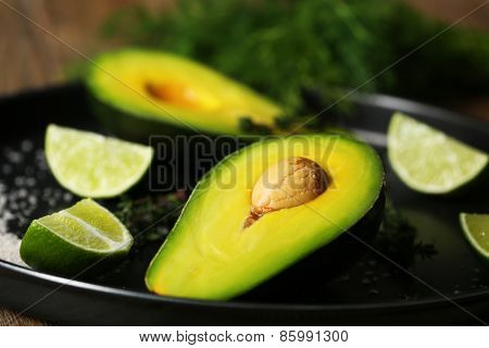 Sliced avocado with lime and herb on metal plate, closeup