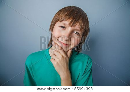 Boy, teenager, twelve years in a green t-shirt , looking away