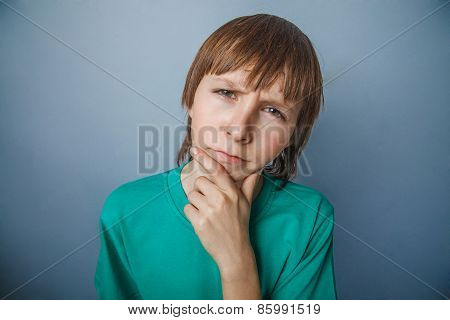 Boy, teenager, twelve years in a green t-shirt, looking away