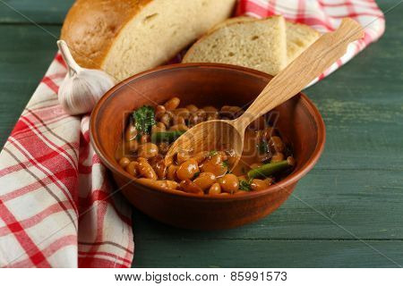 Bean soup in bowl on napkin, on wooden table background
