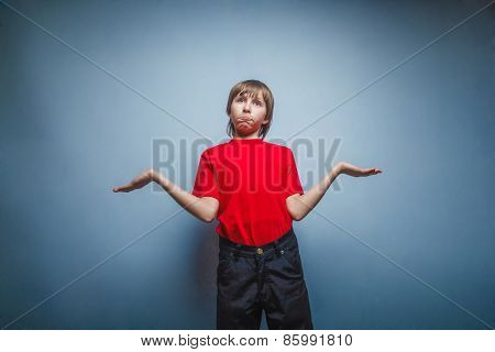 Boy, teenager, twelve years in red T-shirt , threw up his hands