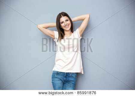 Portrait of a happy young woman over gray background