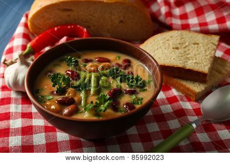 Bean soup in bowl with fresh sliced bread on napkin, on color wooden table background