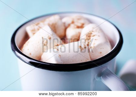Mug of cocoa with marshmallows on wooden table, closeup