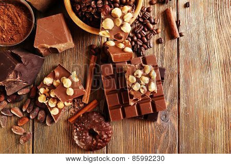 Still life with set of chocolate on wooden table, top view