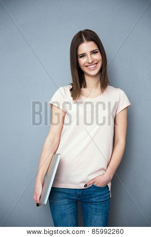 Young woman standing with laptop over gray background