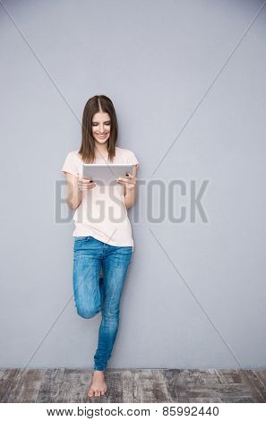 Smiling woman using tablet computer and leaning on the gray wall