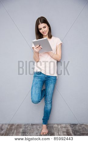 Young woman using tablet computer and leaning on the gray wall