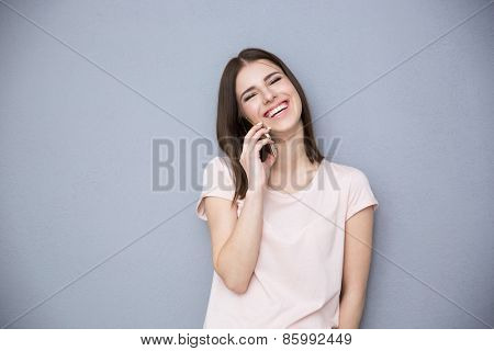 Laughing young woman talking on the phone over gray background