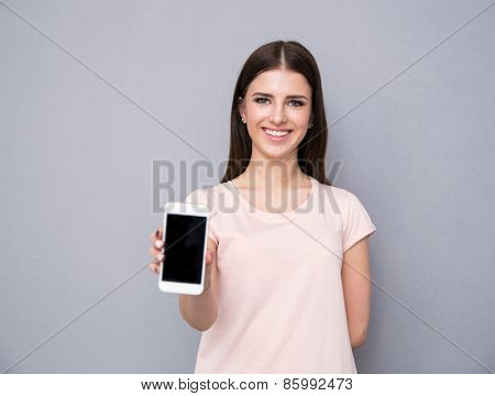 Smiling young woman showing blank smartphone screen