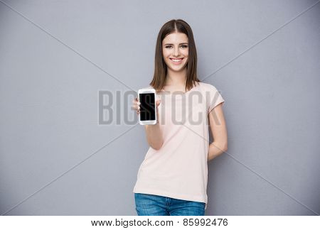 Happy young woman showing blank smartphone screen