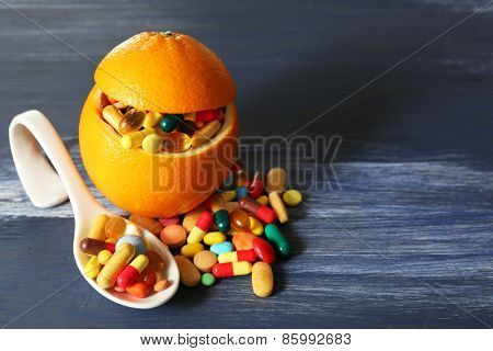 Orange fruit and colorful pills, on wooden background