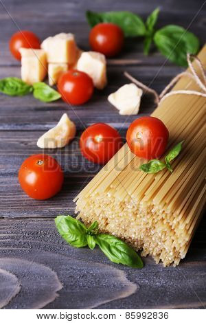 Raw pasta with tomatoes and cheese on wooden background
