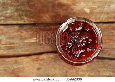 Jar of strawberry jam on wooden background
